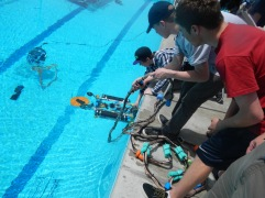 Lowering the ROV into the pool for its underwater missions